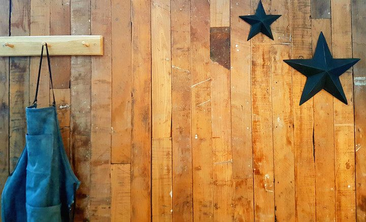 wooden panelled wall with blue apron and black stores.