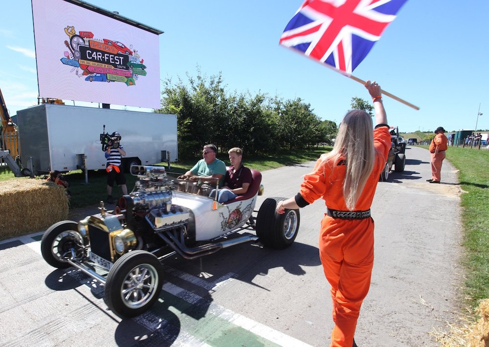 Woman in red jumpsuite waves union jack on race track whilst vintage car arrives at Car Fest.