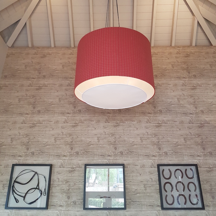 Large red lampshade, bleach wood background. Saddlery.