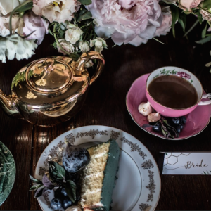 Vintage wedding table lay, pink tea cups, teal damson cake.