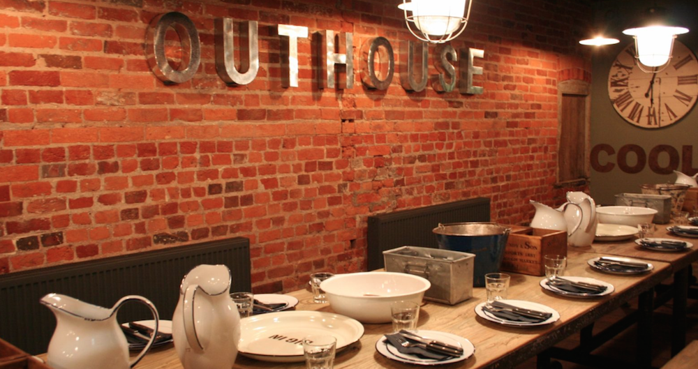 Exposed brick room, dining table, chrome signage.