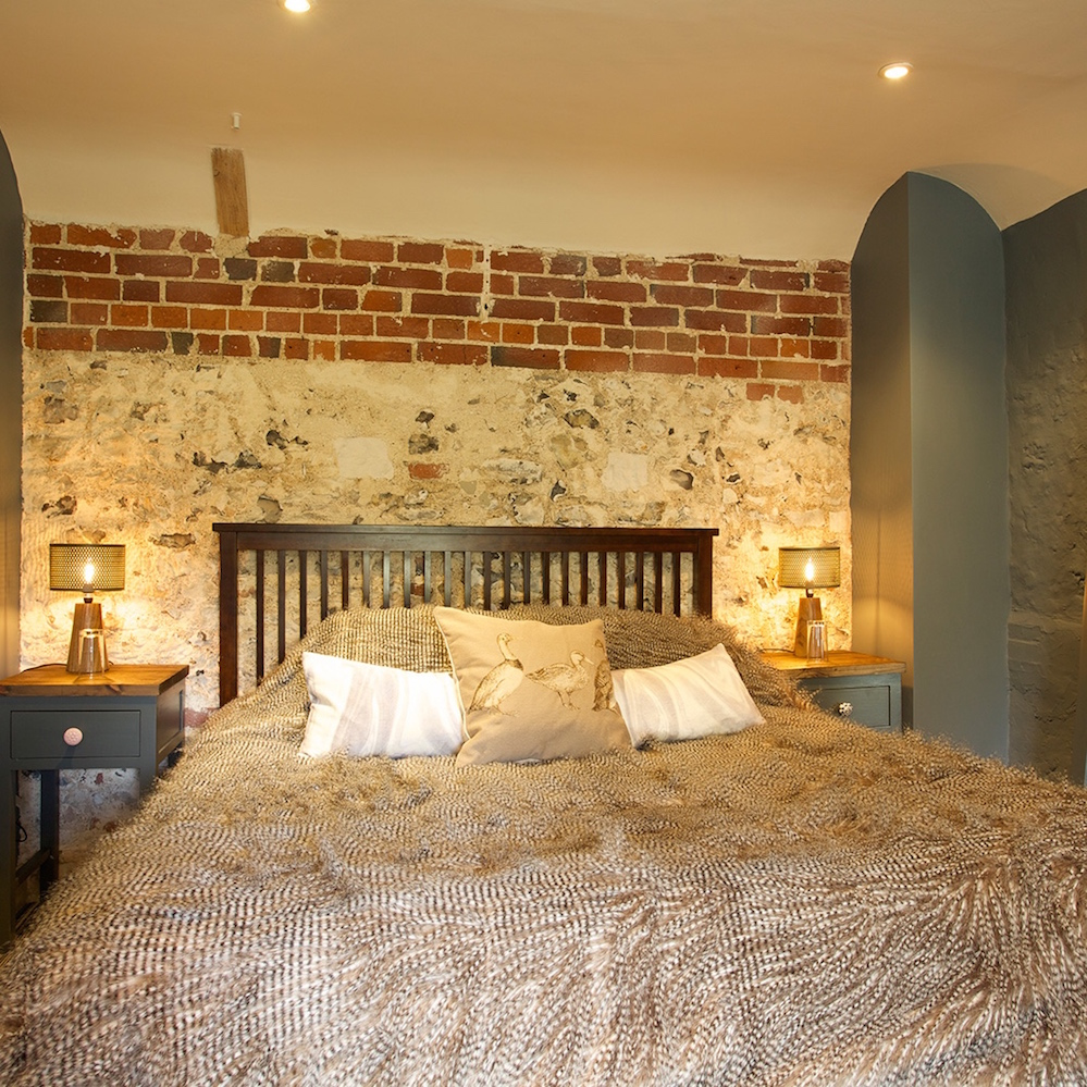 Exposed brickwork, quail feather throw, interiors bedroom.