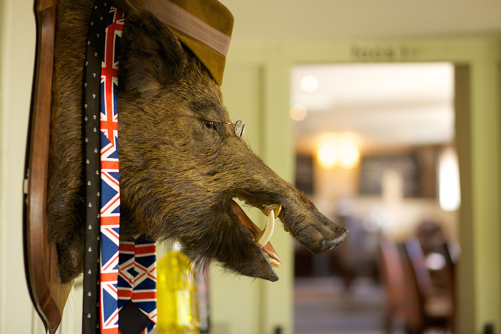 Boar's head with hat on, union jack tie, glasses.