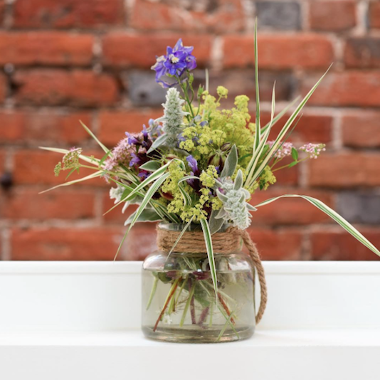 Jam jar flower arrangement against brick wall.