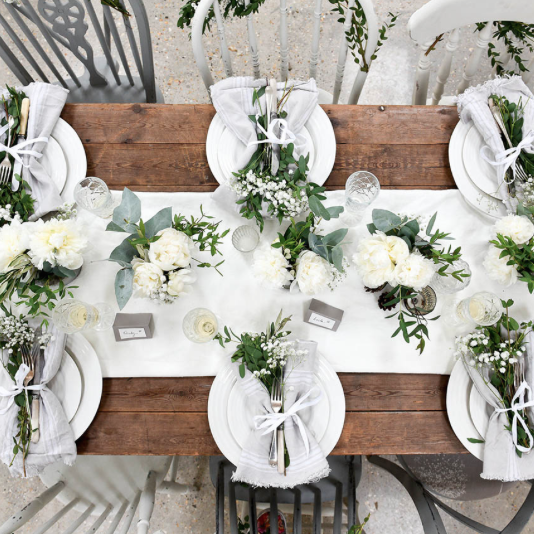 Wedding table setting, greenery, white roses and white crockery.