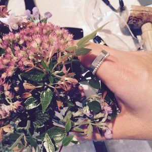 silver stacking rings by flower arrangement.