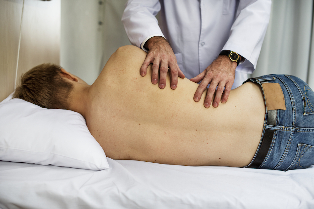 Chiros Health Clinic chiropractor holding mans bare back on bed