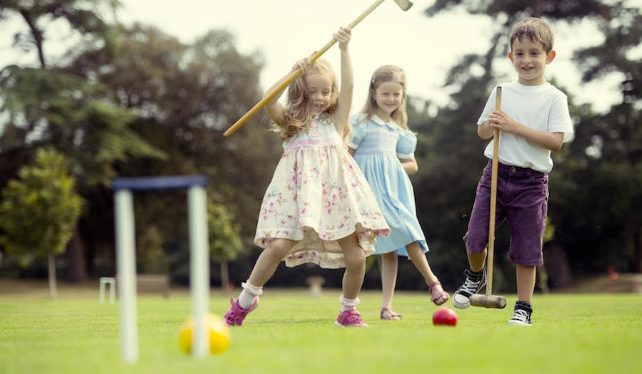 Children playing croquet in a garden.