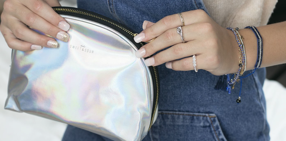 Teen girl in denim holds silver make-up bag.