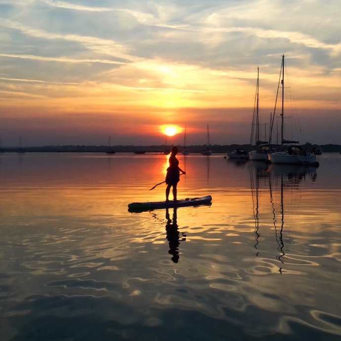 Man paddleboarding in sunset.