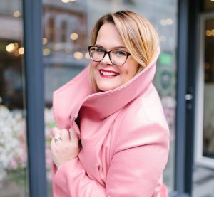 Smiling woman in pink coat.