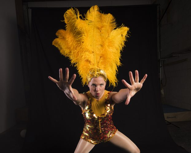 Circus performer with yellow feathers in her hair.