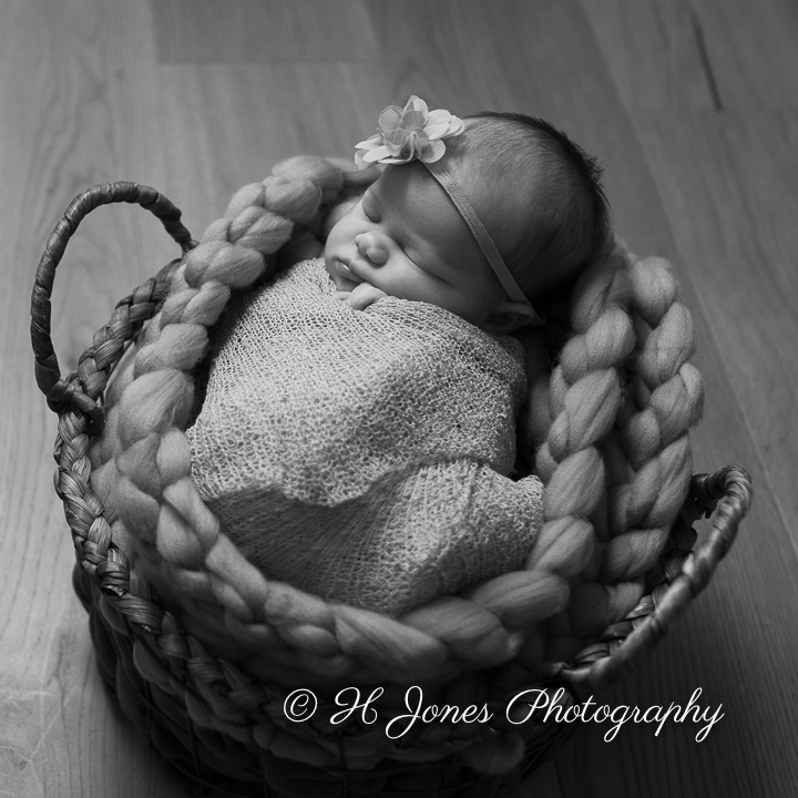 Black & white image of baby girl asleep in a basket.