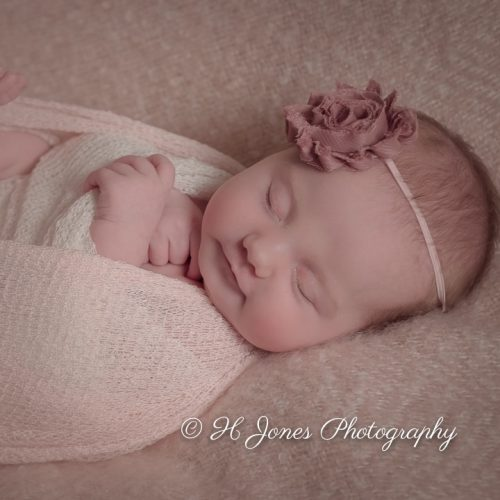 Baby girl asleep with rose in her hair.