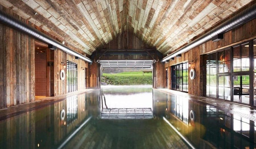 Indoor pool with countryside in distance and distressed wood roof